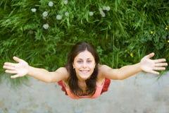 La muchacha feliz se coloca en una hierba verde Imagen de archivo