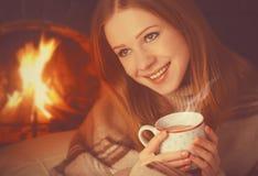 La muchacha feliz se relaja por la chimenea con la taza del té que se calienta, café en invierno Imagen de archivo