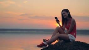 La muchacha feliz se sienta cerca del lago con su teléfono metrajes