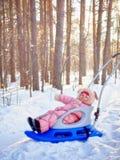 La muchacha feliz sonríe sentándose en el trineo en la nieve Fotografía de archivo