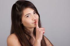 La muchacha feliz sostiene el dedo en sus labios Foto de archivo