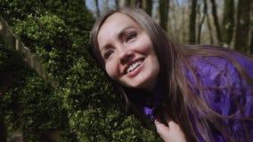 La muchacha feliz toca el musgo verde grueso suave en el árbol con su cara almacen de metraje de vídeo