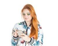 La muchacha feliz utiliza el teléfono móvil con las auriculares Muchacha Redheaded que lleva c Fotografía de archivo