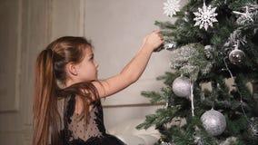 La muchacha feliz viste un árbol de navidad antes del día de fiesta, el bebé está sosteniendo bolas brillantes metrajes