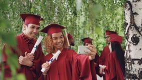 La muchacha feliz y el individuo de la gente joven están tomando el selfie después de la ceremonia de graduación que sostiene los metrajes