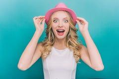 La muchacha feliz y sorprendente está mirando derecho la cámara Ella es muy emocionada La muchacha está sosteniendo el sombrero c Fotos de archivo