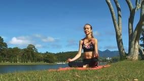 La muchacha fija actitud de la yoga contra el cielo azul del banco verde