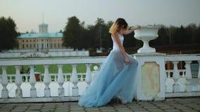 La muchacha flaca atractiva en el vestido blanco y azul va a la barandilla de piedra blanca, toca la maceta con una mano mientras metrajes