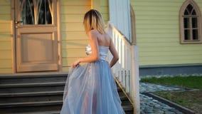 La muchacha flaca hermosa en plata y vestido azul se sostiene en árbol, va arriba a conseguir lista para presentar durante la ses almacen de metraje de vídeo