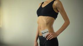 La muchacha flaca que lleva a cabo la nota de la bulimia, cuerpo agotado necesita la ayuda, trastorno alimentario metrajes