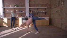 La muchacha flexible feliz hace voltereta gimnástica delante de la mamá y de la hermana en la cocina en casa almacen de metraje de vídeo