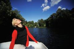 La muchacha flota en un barco y disfruta de la naturaleza Fotografía de archivo