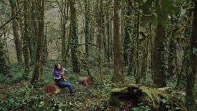 La muchacha frágil está descansando sobre un tocón en un grueso, crecido demasiado con el bosque del musgo y del pantano en las m metrajes