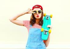 La muchacha fresca de la moda está tirando de sus labios con el monopatín sobre blanco Imágenes de archivo libres de regalías