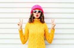 La muchacha fresca de la moda que sopla los labios rojos hace que el aire besa el sombrero amarillo hecho punto colorido del suét Fotos de archivo