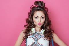 La muchacha fresca de la moda bastante hermosa con los auriculares que llevan la ropa colorida con el pelo rizado sopla un beso c Fotos de archivo