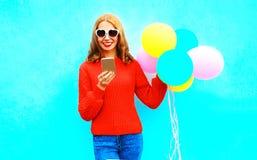 La muchacha fresca está utilizando smartphone con los balones de un aire en un azul Foto de archivo libre de regalías