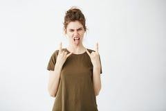 La muchacha fresca joven con el bollo que muestra la lengua y la roca firman la mirada de la cámara sobre el fondo blanco Imagen de archivo libre de regalías