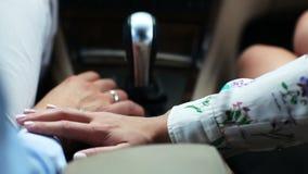 La muchacha frota ligeramente la mano del hombre querido que conduce el automóvil metrajes
