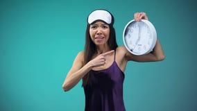 La muchacha frustrada que señala en 7 está en cara de reloj, dormido más de la cuenta y consiguiendo tarde almacen de video