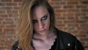 La muchacha fuerte atractiva joven con los ojos ahumados está mirando fijamente la cámara, fondo del ladrillo metrajes