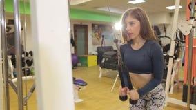 La muchacha fuerte entrena a un tríceps en una cruce en gimnasio almacen de video
