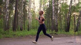 La muchacha fuerte que activa en un atleta muscular del bosque del verano está corriendo en la naturaleza Cámara lenta almacen de metraje de vídeo