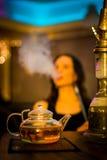La muchacha fuma un té de la cachimba y de la bebida en la barra Imagen de archivo
