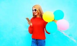La muchacha fummy elegante está utilizando smartphone con los balones de un aire Foto de archivo libre de regalías