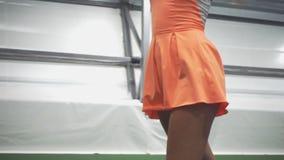 La muchacha golpea la bola con una estafa de tenis y disfruta en la victoria almacen de video