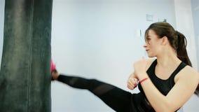 La muchacha golpea el saco de arena del pie, mujer peligrosa en el gimnasio, mujeres hermosas de Kickboxing que entrenan en estud almacen de video