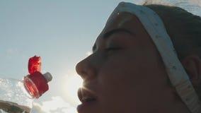 La muchacha gorda bebe el agua de una botella en día soleado almacen de video