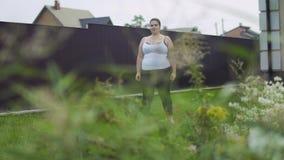 La muchacha gorda está haciendo ejercicios almacen de metraje de vídeo
