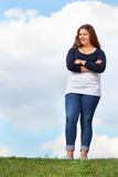 La muchacha gorda joven se coloca en la hierba Fotografía de archivo