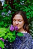 La muchacha goza del olor maravilloso de la lila las flores en manos se están colocando cerca de árbol floreciente de la lila Imagen de archivo