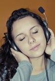 La muchacha goza el escuchar la música con los auriculares Foto de archivo libre de regalías