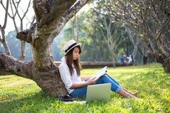 La muchacha goza el leer de un libro debajo del árbol, poniendo en la hierba del parque Fotografía de archivo libre de regalías