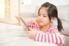La muchacha goza el mirar de la historieta video en el cojín Fotografía de archivo