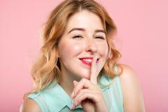 La muchacha guarda el finger secreto del misterio en los labios fotos de archivo