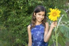 La muchacha guarda el girasol disponible Fotos de archivo libres de regalías