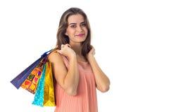 La muchacha guarda en su hombro que los paquetes coloreados multi con los regalos se aíslan un fondo blanco Fotografía de archivo libre de regalías
