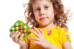 La muchacha guarda las vitaminas Fotos de archivo libres de regalías