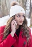 La muchacha habla en el teléfono en el invierno ambiente Foto de archivo