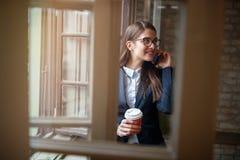 La muchacha habla en el teléfono móvil cerca de ventana dentro Imagen de archivo