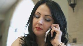 La muchacha habla en el teléfono y escribe en su diario metrajes