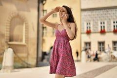 La muchacha habla en el teléfono y mira en la distancia contra Fotografía de archivo