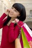 La muchacha habla por el teléfono con muchos bolsos de compras Foto de archivo libre de regalías