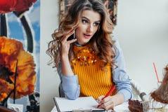 La muchacha habla por el teléfono en un café fotos de archivo