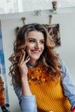 La muchacha habla por el teléfono en un café y una sonrisa foto de archivo libre de regalías