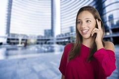La muchacha habla por el teléfono móvil Imagenes de archivo